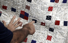 Republican presidential candidate, former Massachusetts Gov. Mitt Romney, points to his signature on a quilt he signed earlier, with messages from supporters, Tuesday, Jan. 31, 2012, at his campaign office in Tampa, Fla. (AP Photo/Charles Dharapak)