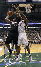 Sacramento Kings center Chuck Hayes (42) attempts a shot while defended by Utah Jazz center Derrick Favors (15) during the second half of an NBA basketball game, Saturday, Jan. 28, 2012, in Salt Lake City. The Utah Jazz won 96-93. (AP Photo/Jim Urquhart)