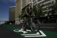 Mayor Ralph Becker rides his bike along 200 South between Main and State Street. Becker is an advocate for the green stripes and has pumped more money and resources into expanding bike lanes throughout the city.  Chris Detrick/The Salt Lake Tribune