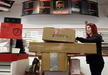 Damian Dovarganes  |  The Associated Press file photo  UPS Store employee Candy Mojica weighs packages before shipping at The UPS Store in the Lake Balboa area of Los Angeles. The unemployment rate fell for the fifth straight month after a surge of January hiring, a promising shift in the nation's outlook for job growth.