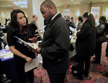 Bebeto Matthews  |  The Associated Press  Daniela Silvero,left, an admissions officer at ASA College, discuss job opportunities with Patrick Rosarie, who is seeking a job in IT, during JobEXPO's job fair, in New York. The unemployment rate fell for the fifth straight month after a surge of January hiring, a promising shift in the nation's outlook for job growth.