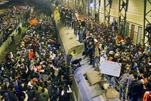 Egyptians crowd a train station waiting for their friends and relatives' arrival from Port Said in Cairo, Egypt, Thursday, Feb. 2, 2012. Witnesses say scores of Egyptian soccer fans were stabbed to death while others suffocated, trapped in a long narrow corridor trying to flee rival fans armed with knives, clubs and stones in the country's worst ever soccer violence. At least 74 people died and hundreds were injured after Wednesday's game in the seaside city of Port Said, when disgruntled fans of the home team, Al Masry, rushed the pitch, setting off clashes and a stampede as riot police largely failed to intervene. A man, right, carries a poster with Arabic that reads,