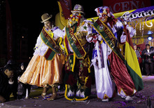 Revelers pose for pictures during an event to elect carnival characters known as Chuta, Pepino and Chola in La Paz, Bolivia Thursday Feb. 2, 2012. (AP Photo/Juan Karita)