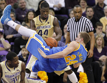 UCLA's Travis Wear (24) flips backward over Washington's Terrence Ross, left, as Darnell Gant moves in to snag the ball in the second half of an NCAA college basketball game Thursday, Feb. 2, 2012, in Seattle. Washington won 71-69. (AP Photo/Elaine Thompson)