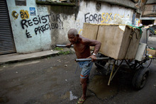 In this photo taken Jan. 31, 2012, a man pushes a cart with goods to recycle past a graffiti that reads in Portuguese