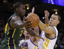 Utah Jazz forward Paul Millsap, left, passes around from Golden State Warriors' David Lee (10) and Andris Biedrins during the first half of an NBA basketball game Thursday, Feb. 2, 2012, in Oakland, Calif. (AP Photo/Ben Margot)
