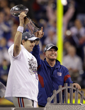 New York Giants quarterback Eli Manning holds the the Vince Lombardi Trophy with head coach Tom Coughlin after the NFL Super Bowl XLVI football game, Sunday, Feb. 5, 2012, in Indianapolis. The Giants won 21-17.  (AP Photo/David Duprey)