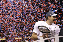 New York Giants quarterback Eli Manning holds up the Vince Lombardi Trophy while celebrating his team's 21-17 win over the New England Patriots in the NFL Super Bowl XLVI football game, Sunday, Feb. 5, 2012, in Indianapolis. (AP Photo/David J. Phillip)