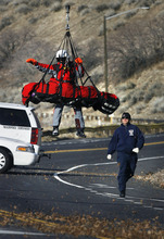 Scott Sommerdorf  |  The Salt Lake Tribune              An injured paraglider pilot is lowered onto Wasatch Boulevard Sunday after he was brought down from the site of his crash, a mountainous area above Pete's Rock. He was repositioned and returned to the chopper for the flight to the hospital.