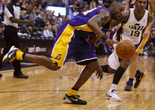 Trent Nelson  |  The Salt Lake Tribune Los Angeles Lakers' Kobe Bryant (24) drives, Utah Jazz guard Raja Bell (19) defending as the Utah Jazz host the Los Angeles Lakers, NBA basketball Saturday, February 4, 2012 at EnergySolutions Arena in Salt Lake City, Utah.