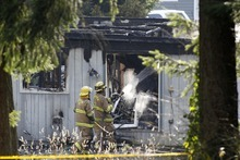 Firefighters spray water on a house near Fredrickson, Wash., Sunday, Feb. 5, 2012, where, according to a sheriff's spokesman, the bodies believed to be Josh Powell and his two sons were found. Days after a judge ruled against him in a child custody hearing, Powell and his sons were killed when police said he appeared to intentionally blow up the house with all three inside ó a tragic ending to a bizarre case that began more than two years ago when the man's wife went mysteriously missing in Utah. (AP Photo/John Froschauer)