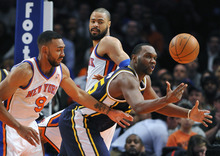 Utah Jazz's Al Jefferson (25) reaches to recover a loose ball as New York Knicks' Jared Jeffries (9) and Tyson Chandler defend during the first half of an NBA basketball game Monday, Feb. 6, 2012, in New York. The Knicks won 99-88. (AP Photo/Kathy Kmonicek)