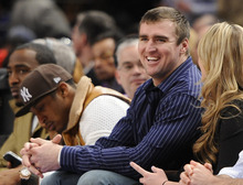 New York Giants' Bear Pascoe, right, watches the NBA basketball game between the Utah Jazz and the New York Knicks on Monday, Feb. 6, 2012, in New York, the day after the Giants defeated the New England Patriots in the NFL football Super Bowl. (AP Photo/Kathy Kmonicek)