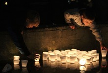 Rick Egan  | The Salt Lake Tribune   Five year-old Wyatt Brown, Tacoma, and Jacob Craven, 8 drop a candles into  McKinley Pond during a vigil  at McKinley Park in Tacoma, Monday, February 6, 2012.  Between 300 and 400 people attended the vigil.