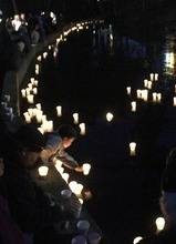 Rick Egan  | The Salt Lake Tribune   Candles are placed into McKinley Pond during a vigil at McKinley Park in Tacoma, Monday, February 6, 2012.  Between 300 and 400 people attended the vigil.