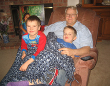 Charlie Powell (left) and Braden Powell sit on the recliner with their grandpa, Chuck Cox, at the Cox home in Puyallup Washington, in this family photo from last January. Photo courtesy of the Cox family