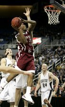 New Mexico State's Wendell McKines, center, goes to the basket as Utah State's Brady Jardine, left, and Tyler Newbold, right, look on during the first half of the men's championship NCAA basketball game at the Western Athletic Conference tournament in Reno, Nev., Saturday, March 13, 2010. (AP Photo/Rich Pedroncelli)