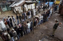 Indian voters stand in a queue to cast their votes as it rains in Gonda, India, Wednesday, Feb. 8, 2012. Residents in India's largest state, Uttar Pradesh, began voting Wednesday in a monthlong local election with repercussions for the whole nation. The state of Uttar Pradesh is so large, with 200 million people, that voting is spread over seven phases and will last until March 3. Results will be declared March 6. (AP Photo/Rajesh Kumar Singh)