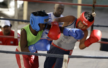 In this photo taken Saturday Jan. 21, 2012, Abraham Fernandez, right, and Andy Lopez exchange punches during their match at a championship tournament in the Rafael Trejos boxing gym in Old Havana, Cuba.  Boxers in Cuba are beginning competition earlier with the addition of a new age category for 9- and 10-year-olds. The boys are part of the pilot program in just Havana for now, but officials say it could be rolled out to the rest of the island, where 11-12 is currently the youngest level of competition. (AP Photo/Javier Galeano)