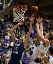 In this photo provided by the University of Portland, BYU's Noah Hartsock (34) reaches for a rebound against Portland's Kevin Bailey (00) and Thomas van der Mars (12) during the first half of their NCAA college basketball game in Portland, Ore., Saturday, Feb. 4, 2012. (AP Photo/University of Portland, Steven Gibbons)