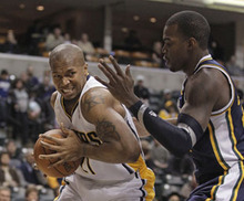 Indiana Pacers' David West drives to the basket against Utah Jazz's Paul Millsap during the first half of an NBA basketball game Tuesday, Feb. 7, 2012, in Indianapolis. (AP Photo/Darron Cummings)