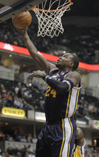 Utah Jazz's Paul Millsap puts up a shot against Indiana Pacers' Roy Hibbert, behind, during the second half of an NBA basketball game Tuesday, Feb. 7, 2012, in Indianapolis. Indiana won 104-99. (AP Photo/Darron Cummings)
