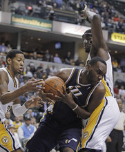 Utah Jazz's Al Jefferson goes to the basket against Indiana Pacers' Danny Granger, left, and Roy Hibbert during the second half of an NBA basketball game Tuesday, Feb. 7, 2012, in Indianapolis. Indiana won 104-99. (AP Photo/Darron Cummings)