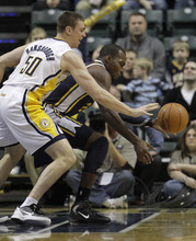 Utah Jazz's Paul Millsap works against Indiana Pacers' Tyler Hansbrough during the first half of an NBA basketball game Tuesday, Feb. 7, 2012, in Indianapolis. (AP Photo/Darron Cummings)