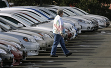 FILE - In this Feb. 18, 2007 file photo, an unidentified buyer searches through long lines of unsold 2007 Camry sedans at a Toyota dealership in Boulder, Colo. Federal safety regulators are investigating reports of fires in the driver's side doors of 2007 Toyota Camry sedans and RAV-4 crossover SUVs. The National Highway Traffic Safety Administration said Friday, Feb. 10, 2012, the problem could affect 830,000 vehicles. (AP Photo/David Zalubowski, file)