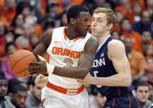 Syracuse's Dion Waiters, left, drives against Connecticut's Niels Giffey during the first half of an NCAA college basketball game in Syracuse, N.Y., Saturday, Feb. 11, 2012. (AP Photo/KevinRivoli)