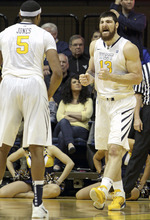 West Virginia's Deniz Kilicli (13) celebrates with teammate Kevin Jones (5) after making a basket against Louisville during the first half of an NCAA college basketball game at WVU Coliseum in Morgantown, W.Va., on Saturday, Feb. 11, 2012. (AP Photo/David Smith)