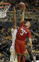 Louisville's Peyton Siva (3) goes up for a basket attempt over West Virginia's Kevin Jones, left, during the first half of an NCAA college basketball game at WVU Coliseum in Morgantown, W.Va., on Saturday, Feb. 11, 2012. (AP Photo/David Smith)