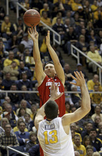 Louisville's Kyle Kuric, top, shoots over West Virginia's Deniz Kilicli (13) during the first half of an NCAA college basketball game at WVU Coliseum in Morgantown, W.Va., on Saturday, Feb. 11, 2012. (AP Photo/David Smith)