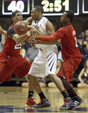 West Virginia's Keaton Miles, center, is double-teamed by Louisville's Wayne Blackshear (25) and Russ Smith, right, during the first half of an NCAA college basketball game at WVU Coliseum in Morgantown, W.Va., on Saturday, Feb. 11, 2012. (AP Photo/David Smith)