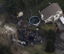 The smoldering remains of a house, left, where an explosion killed Josh Powell and his two sons, Sunday, Feb. 5, 2012, is shown from the air in Graham, Wash. The explosion occurred moments after a Child Protective Services worker brought the two boys to the home for a supervised visit. Powell's wife Susan went reportedly missing from their West Valley City, Utah, home in December 2009. (AP Photo/Ted S. Warren)