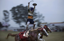 In this Saturday, Feb.11, 2012 photo, a Sikh warrior, riding on two horses, performs during a rural sports festival, also known as