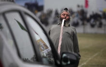 In this Saturday, Feb.11, 2012 photo, an Indian villager pulls a car with his teeth during a rural sports festival, also known as