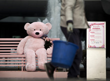 A cleaner carrying a bucket of water walks past a huge teddy bear with bouquet of roses put on a bench for visitors to photograph with them outside a shopping mall ahead of Valentine's day in Beijing, China, Sunday, Feb. 12, 2012. (AP Photo/Andy Wong)