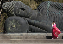 A temple maiden pays respect to a 16-meter, 30-ton bronze statue of reclining Buddha at Jorakuzan Mantokuji temple in Tateyama, east of Tokyo, Sunday, Feb. 12, 2012. It is said a believer can fulfill a dream if the person touches foot of the statue after going around it three times clockwise. (AP Photo/Itsuo Inouye)