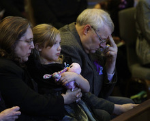Ted S. Warren  |  The Associated Press Chuck Cox and his wife, Judy, hold their granddaughter Dakota, 6, during a funeral service for their grandsons Charlie and Braden Powell Saturday in Tacoma, Wash. The boys died Feb. 5, 2012, when their father, Josh Powell, set fire to the home he was living in while they visited.
