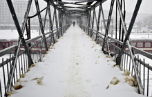 A man crosses a footbridge at the main railway station in Bucharest, Romania, Monday, Feb. 13, 2012. Military planes flew in tons of emergency food Monday to towns and villages in eastern Romania, where thousands have been stranded. Some people were cutting tunnels through up to 15 feet (4 meters) of snow to get out of their homes. (AP Photo/Vadim Ghirda)