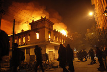Protesters pass by a burning cinema in Athens, Sunday, Feb. 12, 2012. Riots engulfed central Athens and at least 10 buildings went up in flames in mass protests late Sunday as lawmakers prepared for a historic parliamentary vote on harsh austerity measures demanded to keep the country solvent and within the eurozone. (AP Photo/Kostas Tsironis)