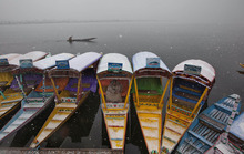 A Kashmiri Muslim man waits for customers as he sits on a shikara, or boat,  on the shores of Dal Lake during snowfall in Srinagar, India, Monday, Feb. 13, 2012. The Jammu-Srinagar highway has been blocked because of heavy snowfall in the region, according to news reports. (AP Photo/Dar Yasin)