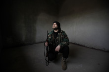 A Syrian rebel looks out after Syrian army tanks enter the northwestern city of Idlib, Syria, Tuesday, Feb. 14, 2012. Syrian government forces renewed their assault on the rebellious city of Homs on Tuesday in what activists described as the heaviest shelling in days, as the U.N. human rights chief raised fears of civil war. (AP Photo)