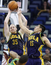New Orleans Hornets center Chris Kaman (35) rebounds the ball over forward Gustavo Ayon (15) in the second half of an NBA basketball game in New Orleans, Monday, Feb. 13, 2012. The Hornets won their fifth game this season 86-80. Chris Kaman led the Hornets with 27 points. (AP Photo/Jonathan Bachman)