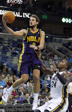 New Orleans Hornets guard Marco Belinelli (8) scores over Utah Jazz power forward Paul Millsap (24) in the second half of an NBA basketball game in New Orleans, Monday, Feb. 13, 2012. The Hornets won their fifth game this season 86-80.(AP Photo/Jonathan Bachman)