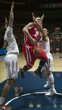 Utah's Javon Dawson (21) tries to control the ball between Arizona's Nick Johnson, right, and Jesse Perry (33) during the second half of an NCAA college basketball game in Tucson, Ariz., Saturday, Feb. 11, 2012. Arizona won 70-61. (AP Photo/John Miller)