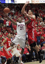 Arizona's Kyle Fogg (21) shoots over Jason Washburn (42) during the second half of an NCAA college basketball game at McKale Center in Tucson, Ariz., Saturday, Feb. 11, 2012.  Arizona won 70-61.(AP Photo/Wily Low)