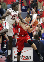 Utah's Jason Washburn, right, grabs a rebound against Arizona's Angelo Chol (30) during the second half of an NCAA college basketball game in Tucson, Ariz., Saturday, Feb. 11, 2012. Arizona won 70-61. (AP Photo/John Miller)