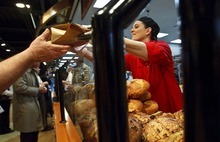 Leah Hogsten  |  The Salt Lake Tribune Artisan bread tech Lora Powell hands out free loaves of bread on Wednesday during the opening of the new Harmons grocery store  in downtown Salt Lake City. The store at 100 S. 135 East was built on two levels. A 50,000-square-foot ground level features a large produce department and meat counter with fresh fish. On the 18,000-square-foot mezzanine there is a deli with a seating capacity for about 300 customers.